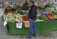 Man is selling fruits and vegetables outdoor in Malmo, Sweden. Malmo, Sweden - April 22, 2017: man is selling fruits and vegetables outdoor in Malmo, Sweden Royalty Free Stock Photo