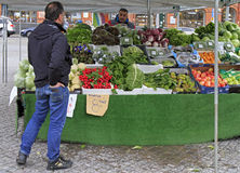 Man is selling fruits and vegetables outdoor in Malmo, Sweden. Malmo, Sweden - April 22, 2017: man is selling fruits and vegetables outdoor in Malmo, Sweden Stock Image
