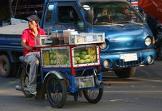 Laotian man is selling tropical fruits at a tricycle, Vientiane, Laos Stock Image
