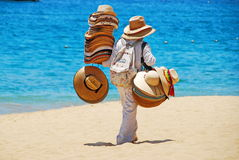 Man Selling Hats on Beach. Local Mexican man selling straw hats and colorful baskets on the beach in Cabo San Lucas, Mexico, backed by the brilliant blue Pacific Stock Photo