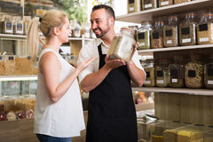 Man selling herbs and spices in organic store. Friendly smiling men in apron selling herbs and spices to a female customer in organic food store royalty free stock image