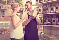 Man selling herbs and spices in organic store. Friendly smiling men in apron selling herbs and spices to a female customer in organic food store stock images