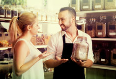 Man selling herbs and spices in organic store. Positive male seller in apron selling herbs and spices to a female customer in organic food store royalty free stock photography