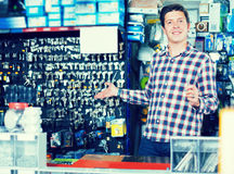 Man selling keys in hardware shop. Positive young man standing near the counter and selling keys in hardware shop Royalty Free Stock Image