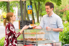 Man selling pizza by slice. A street food vendor selling pizza by slice outdoors stock photography