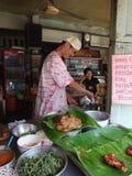 Man selling Thai food, Thailand. BANGKOK, THAILAND - MAY 18: Man preparing food in an open roadside restaurant. May 18, 2005 in Bangkok Stock Images