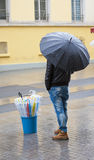 Man selling umbrellas stood in street. Man stood in rain on street selling umbrellas Royalty Free Stock Images