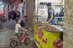 Man sells baking to boy in eastern market, Kashan, Iran. stock photo