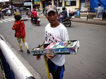 A man sells cigarettes, candies and snack items along a street in Antipolo City. ANTIPOLO CITY, PHILIPPINES - JULY 19, 2017: A man sells cigarettes, candies and stock photos