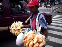 A man sells cigarettes, candies and snack items along a street in Antipolo City. ANTIPOLO CITY, PHILIPPINES - JULY 19, 2017: A man sells cigarettes, candies and royalty free stock photography