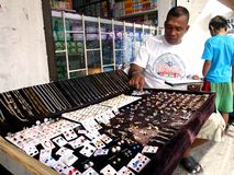 A man sells different kind of jewelries at a sidewalk Stock Image