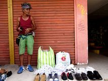 A man sells different kind of shoes at a sidewalk Royalty Free Stock Photography