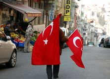 Man sells flags of Turkey. ISTANBUL, TURKEY - NOV 22, 2011 - Man sells Turkish flags on the streets of Istanbul Royalty Free Stock Photography