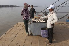 Man sells fried bananas at the ferryboat in Cambodia. Crossing Mekong river Stock Photo