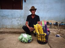 A man sells plastic clothes hangers at a sidewalk along a street in Antipolo City. ANTIPOLO CITY, PHILIPPINES - JULY 19, 2017: A man sells plastic clothes stock image