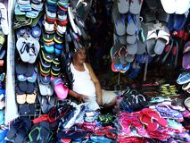 A man sells a wide variety of rubber slippers and sandals in his store in Antipolo City. ANTIPOLO CITY, PHILIPPINES - APRIL 24, 2017: A man sells a wide variety stock photography