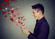 Man sending love messages on mobile phone hearts flying away Royalty Free Stock Images
