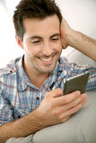 Man sending message on smartphone from home Stock Image