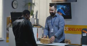 Man sending a package in a delivery center. Medium shot of a young men sending a package in a delivery center royalty free stock photo