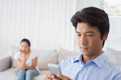 Man sending a text while girlfriend watches from couch Stock Images