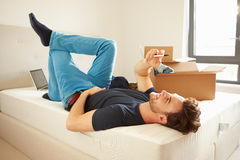 Man Sending Text Message Having Moved Into New Home. Looking Up At Mobile Phone royalty free stock photos