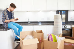 Man Sending Text Message Having Moved Into New Home Royalty Free Stock Image