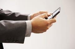 Man sending text messages. Man holding a hand phone sending text messages Stock Image