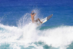 A Man Sends Spray into the Air while Surfing. A young man catches air while surfing in Hawaii Royalty Free Stock Photos