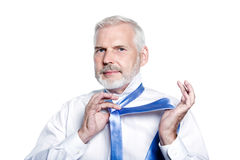 Man senior getting dressed tying windsor necktie. Windsor necktie lesson doing by an handsome man senior getting dressed on isolated white background Royalty Free Stock Photography