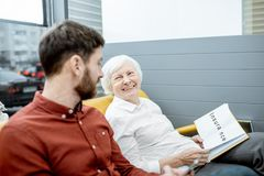 Man and senior woman at the hospital reception. Man with smiling senior women holding insurance at the hospital reception royalty free stock image