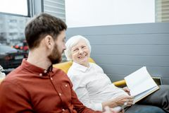 Man and senior woman at the hospital reception. Man with smiling senior women waiting for the doctor at the hospital reception stock photos