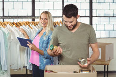 Man separating products while woman holding digital tablet Royalty Free Stock Photo
