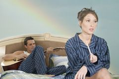 Man serenading woman. Young couple in bed with the man playing guitar and the woman looking not so happy about it royalty free stock photo
