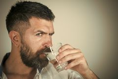 Man with serious emotion. Man with long beard hold water glass on grey background. Health and dieting. Life source and healthcare. Hangover and thirst. Hipster stock photography