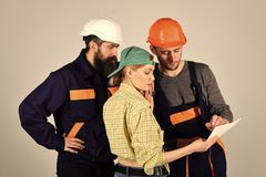 Man with serious emotion. Recruitment concept. Brigade of workers, builders in helmets, repairers and lady discussing. Contract, grey background Stock Photography