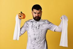Man with serious face expression on yellow background. October time and spooky holiday concept. Halloween character in white long sleeved ghost costume. Guy royalty free stock photography