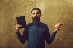 Man with serious face hold notebook and money box. Man or businessman with serious face hold notebook and money box on beige background stock photos