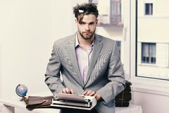 Man with serious face types story or business report. Young author or editor writes story on old typewriter on window background. Editing and writing concept Royalty Free Stock Image