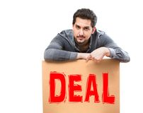 A man with a serious gaze pointing his finger on a deal marketing sign, perfect for advertising, promotion, banner. A man with a serious gaze pointing his finger Royalty Free Stock Images
