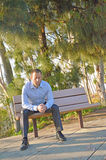 Man in serious prayer. Man in prayer with his hands folded outside in a park while sitting on a bench stock photos