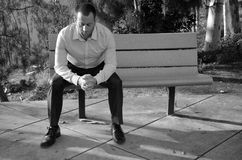 Man in serious prayer. Man in prayer with his hands folded outside in a park while sitting on a bench Royalty Free Stock Photography