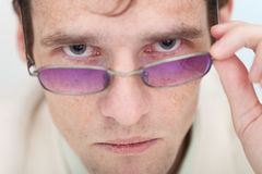 Man seriously looks at us over glasses Stock Photo