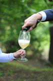 Man serves champagne to his woman. Man hand serves champagne to his woman glass in the green park, wedding event, outdoor picnic Royalty Free Stock Photos