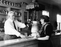 Man serving beverage to woman at counter Stock Image