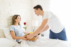 Man Serving Breakfast To Beautiful Woman In Bed. Loving men serving breakfast to beautiful women in bed at home Royalty Free Stock Images