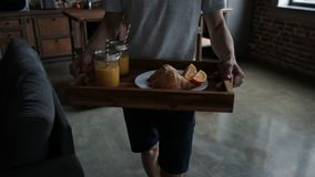 Man serving breakfast on wooden tray in bed. Close-up midsection of young man carrying breakfast on wooden tray. Male hands holding wooden tray with orange juice stock footage