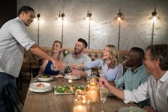 Man serving champagne to his friends Stock Photos