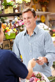 Man serving customer in florist. Taking payment Royalty Free Stock Images