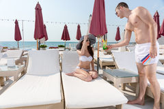 Man Serving Drink to Woman on Deck of Beach Resort Stock Photo
