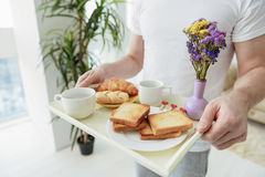 Man serving food to his lover in the morning. Romantic breakfast in bed. Close up of male hands holding tray with fresh pastry, cups of coffee and flowers Royalty Free Stock Image